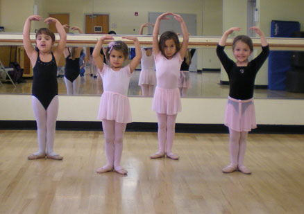 Four young girls participating in a ballet class