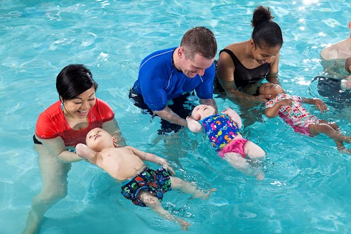 Three adults and three babies participating in a swimming class